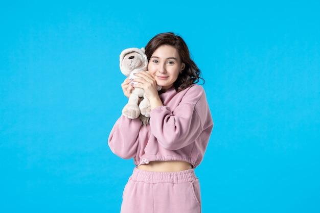 Vooraanzicht jonge vrouw in roze pyjama met kleine speelgoedbeer op blauwe nachtkleur slapeloosheid droom rust bed vrouw feest