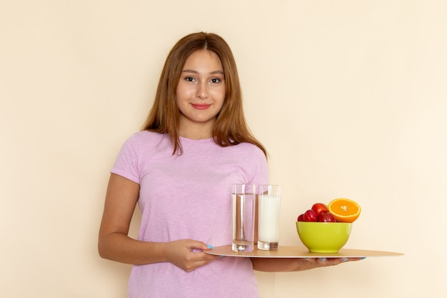 Vooraanzicht jonge vrouw in roze t-shirt en spijkerbroek met dienblad fruit melk en water op grijs