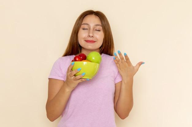 Vooraanzicht jonge vrouw in roze t-shirt en spijkerbroek met plaat met fruit