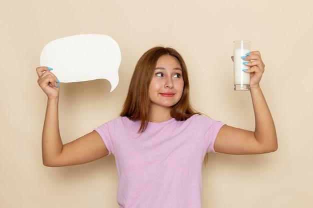 Vooraanzicht jonge vrouw in roze t-shirt en spijkerbroek met wit bord en melk op grijs