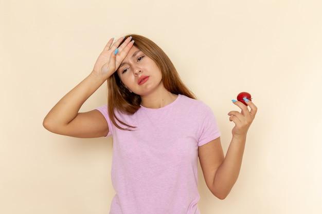 Vooraanzicht jonge vrouw in roze t-shirt en spijkerbroek met zure pruim slecht gevoel