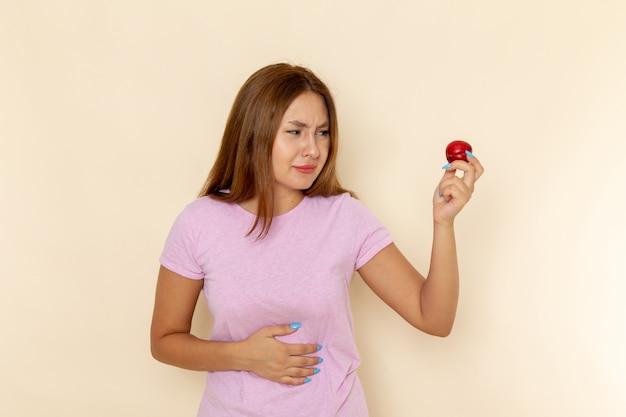 Vooraanzicht jonge vrouw in roze t-shirt en spijkerbroek met zure pruim