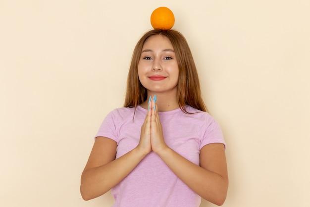 Vooraanzicht jonge vrouw in roze t-shirt en spijkerbroek oranje op haar hoofd houden en bidden
