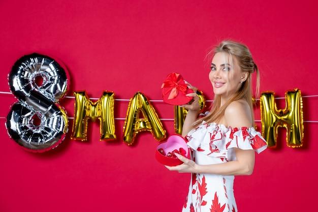 Vooraanzicht jonge vrouw in schattige jurk die aanwezig is en opent op versierde rode schoonheidsvrouwendagkleur