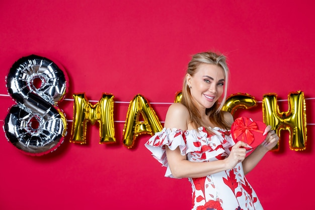 Vooraanzicht jonge vrouw in schattige jurk die aanwezig is op versierd rood