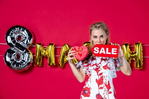 Vooraanzicht jonge vrouw in schattige jurk met cadeau en verkoopnaambordje op rode boodschappen