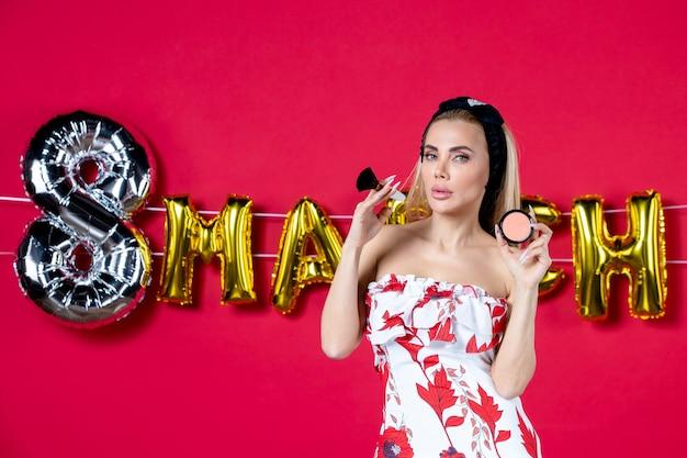 Vooraanzicht jonge vrouw in schattige jurk met kwast en poeder voor op rode lippen model