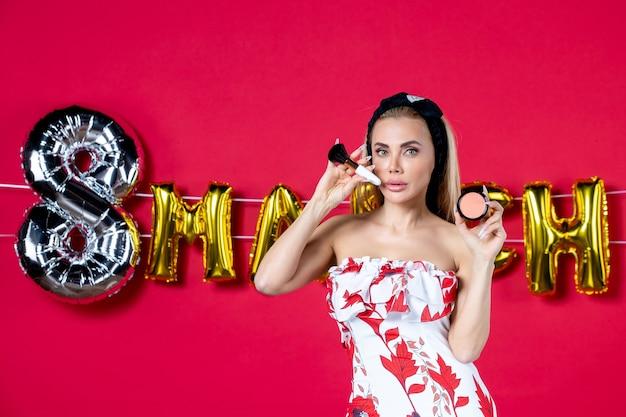 Vooraanzicht jonge vrouw in schattige jurk met kwast en poeder voor op rood model