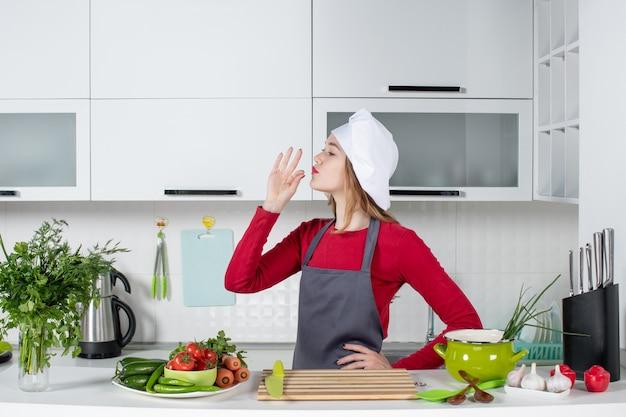 Vooraanzicht jonge vrouw in schort die chef-kok kusteken maakt