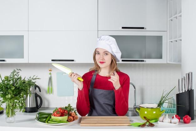 Vooraanzicht jonge vrouw in schort die mes omhoog houdt