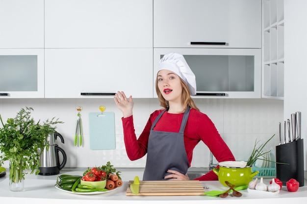 Vooraanzicht jonge vrouw in schort wijzend op keukenkast