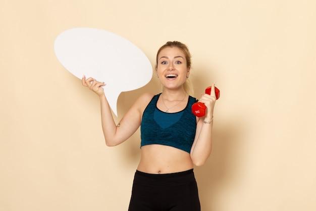 Vooraanzicht jonge vrouw in sport outfit met halters en witte tekstballon
