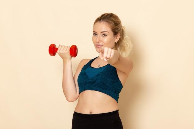 Vooraanzicht jonge vrouw in sport outfit met rode halters op witte muur gezondheid sport lichaam schoonheid training