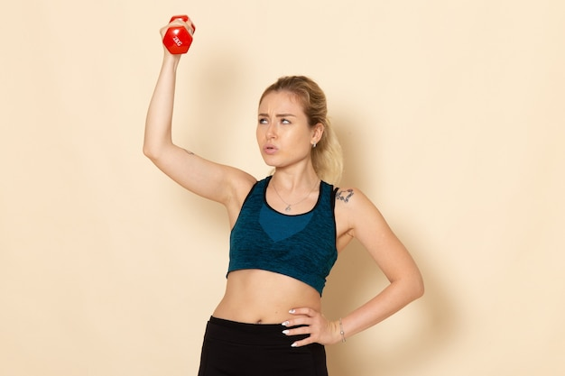 Vooraanzicht jonge vrouw in sport outfit met rode halters op witte muur sport lichaam gezondheid schoonheid training vrouw