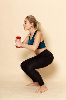 Vooraanzicht jonge vrouw in sport outfit werken met halters