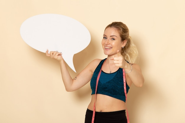 Vooraanzicht jonge vrouw in sport outfit wit bord houden en glimlachen