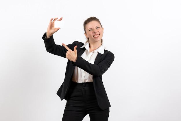Vooraanzicht jonge vrouw in strikt klassiek pak met witte kaart op witte achtergrond job business vrouwelijke werk kostuum vrouw