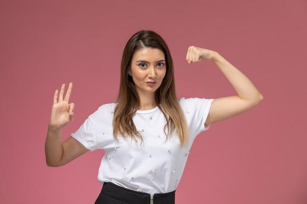 Vooraanzicht jonge vrouw in wit overhemd buigen op roze muur kleur vrouw pose model
