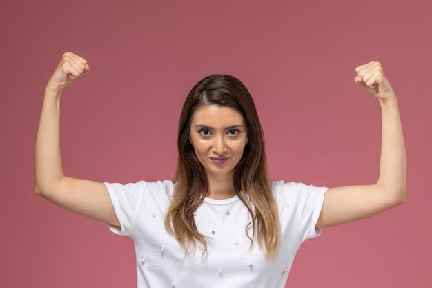 Vooraanzicht jonge vrouw in wit overhemd buigen op roze muur