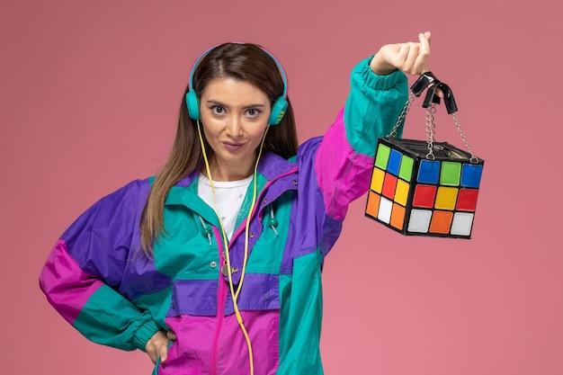 Vooraanzicht jonge vrouw in wit overhemd gekleurde jas luisteren naar muziek bedrijf tas op roze muur, kleur vrouw pose model