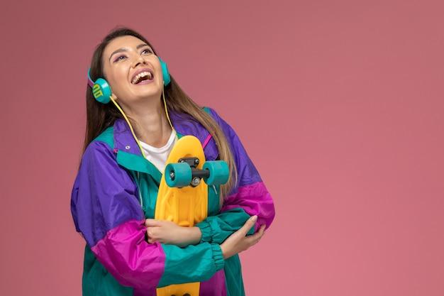 Vooraanzicht jonge vrouw in wit overhemd gekleurde jas luisteren naar muziek lachend op roze muur, kleur vrouw pose model