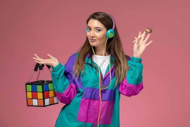 Vooraanzicht jonge vrouw in wit overhemd kleurrijke jas bedrijf tas op lichtroze muur, vrouw model vrouw pose