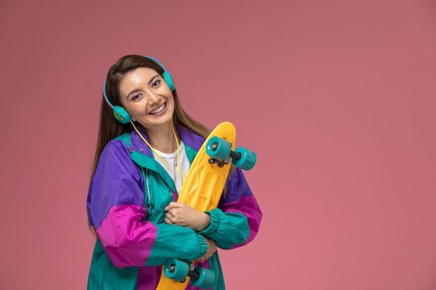 Vooraanzicht jonge vrouw in wit overhemd kleurrijke jas luisteren naar muziek en skateboard te houden