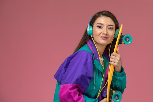 Vooraanzicht jonge vrouw in wit overhemd kleurrijke jas luisteren naar muziek met glimlach, kleur vrouw pose model vrouw