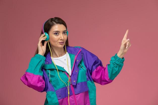 Vooraanzicht jonge vrouw in wit overhemd kleurrijke jas luisteren naar muziek op de roze muur foto kleur vrouw pose model