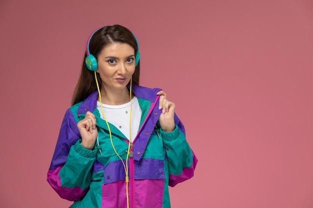 Vooraanzicht jonge vrouw in wit overhemd kleurrijke jas luisteren naar muziek poseren op de roze muur foto kleur vrouw pose model