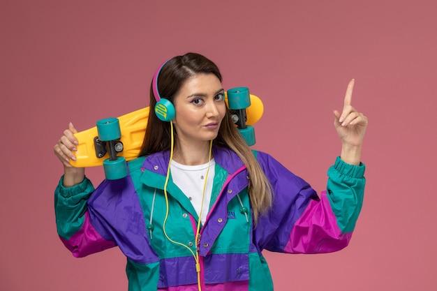 Vooraanzicht jonge vrouw in wit overhemd kleurrijke jas met skateboard