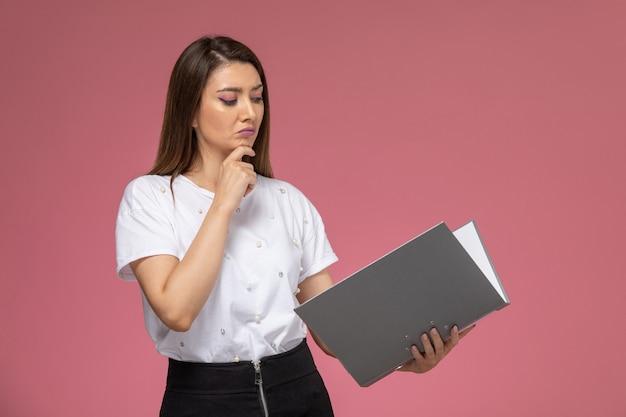 Vooraanzicht jonge vrouw in wit overhemd lezing grijs document op de roze muur, kleur vrouw pose model vrouw