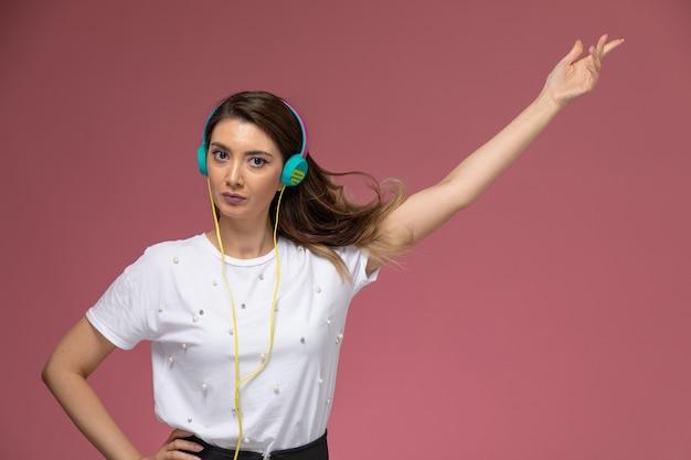 Vooraanzicht jonge vrouw in wit overhemd luisteren naar muziek en dansen op de roze muur, kleur vrouw pose model vrouw