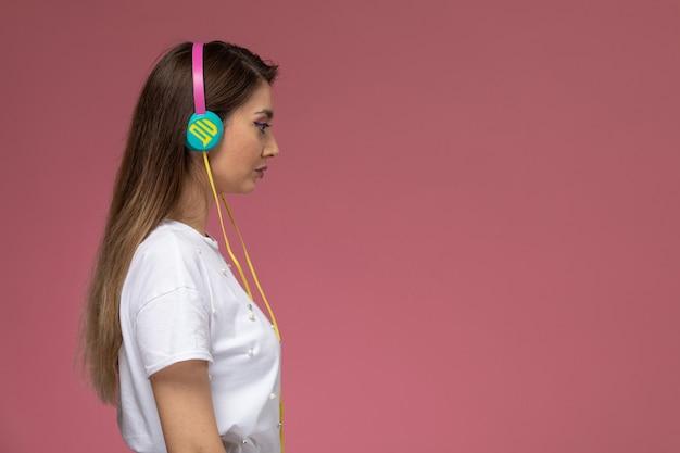 Vooraanzicht jonge vrouw in wit overhemd luisteren naar muziek met haar koptelefoon op de roze muur, kleur vrouw pose model vrouw