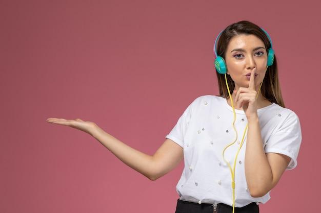 Vooraanzicht jonge vrouw in wit overhemd luisteren naar muziek met stilte teken op de roze muur, model vrouw