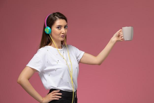Vooraanzicht jonge vrouw in wit overhemd luisteren naar muziek op de roze muur, kleur model vrouw pose vrouw