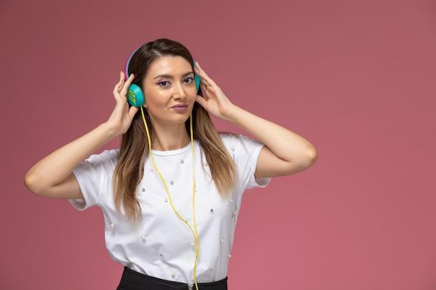Vooraanzicht jonge vrouw in wit overhemd luisteren naar muziek op de roze muur, kleur vrouw pose model vrouw