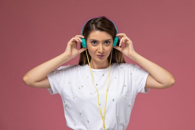 Vooraanzicht jonge vrouw in wit overhemd luisteren naar muziek via haar gekleurde oortelefoons op de roze muur, kleur vrouw model poseren vrouw