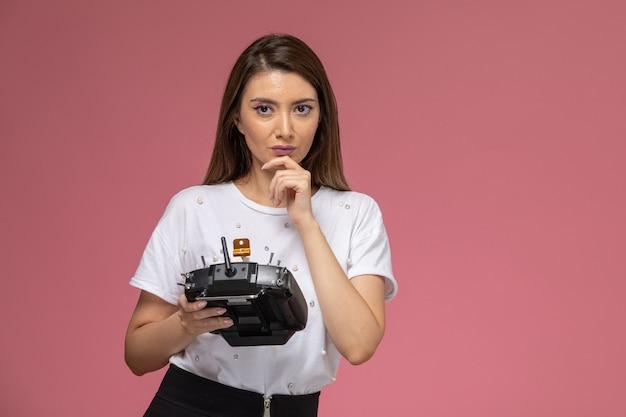 Vooraanzicht jonge vrouw in wit overhemd met afstandsbediening denken