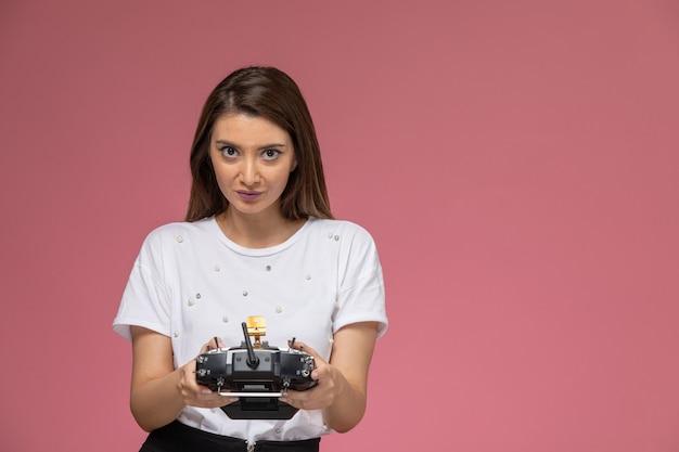 Vooraanzicht jonge vrouw in wit overhemd met afstandsbediening