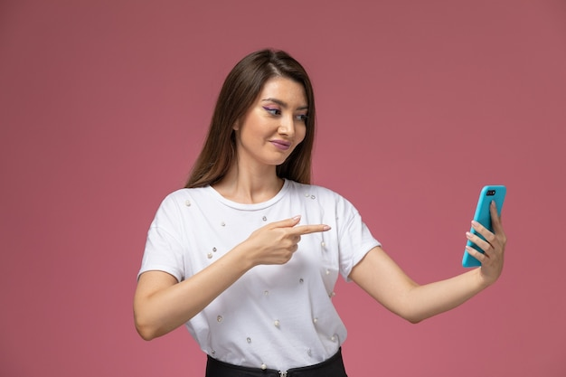 Vooraanzicht jonge vrouw in wit overhemd met behulp van haar telefoon op de roze muur, de kleurenvrouw stelt modelvrouw