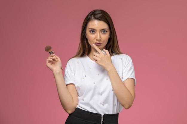 Vooraanzicht jonge vrouw in wit overhemd met make-up borstel op de roze muur, foto kleur vrouw pose model