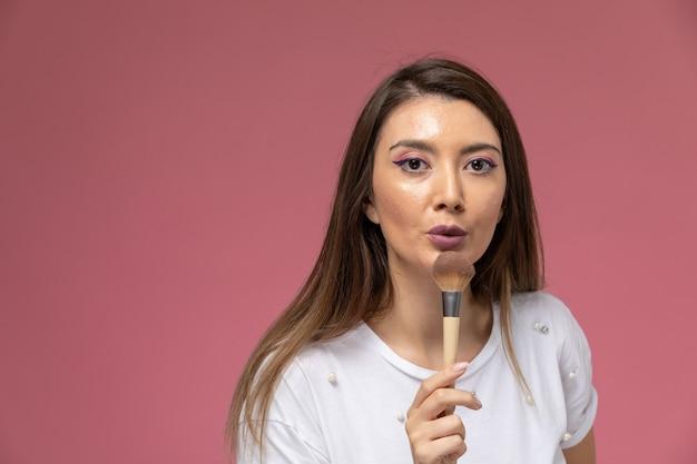 Vooraanzicht jonge vrouw in wit overhemd met make-up borstel op de roze muur, kleur vrouw pose model