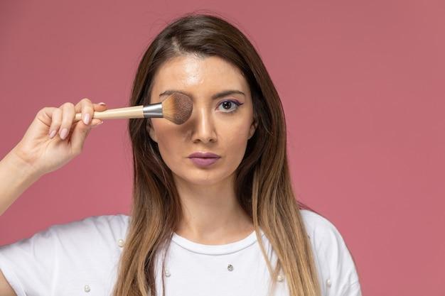 Vooraanzicht jonge vrouw in wit overhemd met make-up borstel op roze, model vrouw pose meisje schoonheid