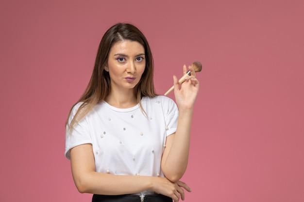Vooraanzicht jonge vrouw in wit overhemd met make-up borstel