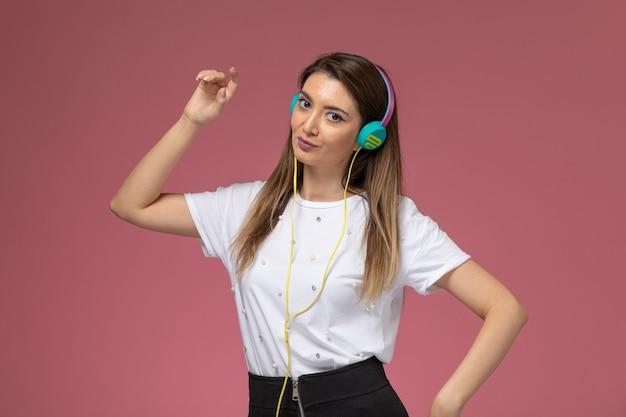 Vooraanzicht jonge vrouw in wit overhemd poseren en luisteren naar muziek op de roze muur, kleur vrouw model