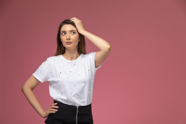 Vooraanzicht jonge vrouw in wit overhemd poseren op de roze muur, kleur vrouw pose model