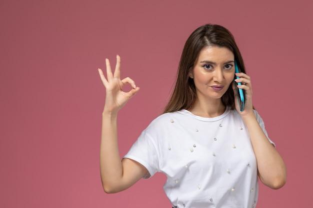 Vooraanzicht jonge vrouw in wit overhemd poseren praten aan de telefoon op roze muur, foto kleur vrouw pose model