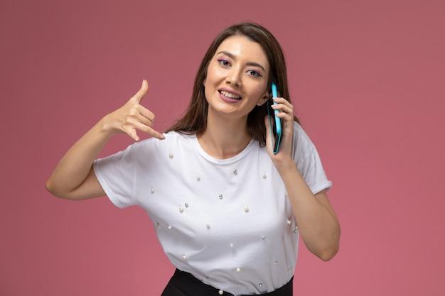 Vooraanzicht jonge vrouw in wit overhemd praten aan de telefoon lachend op de roze muur