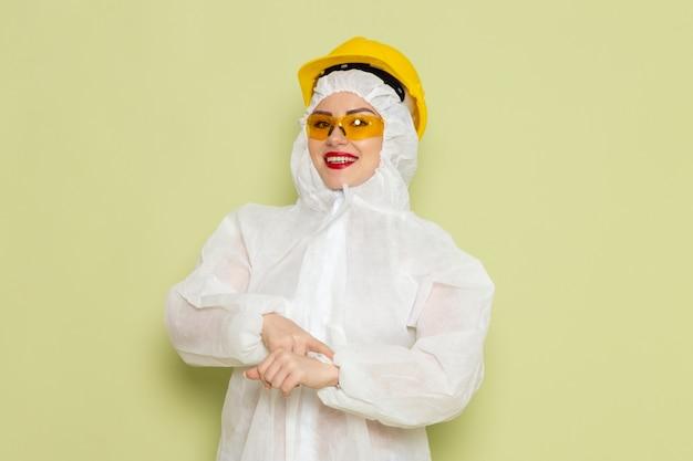 Vooraanzicht jonge vrouw in wit speciaal pak en gele helm glimlachend wijzend in haar pols op de groene ruimte s